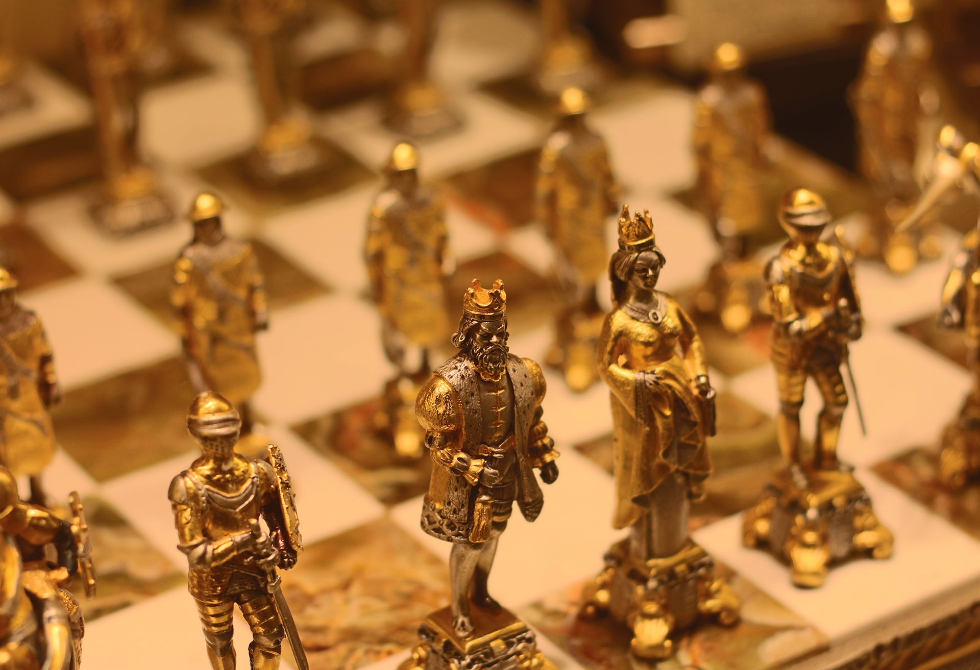 chess figures on a chess board; made of metal and painted in gold, showing in detail a king, queen, soldiers